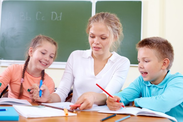 teacher-helping-students-in-class_1098-1855