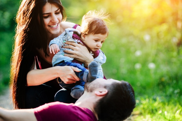 woman-with-a-baby-in-her-arms-while-her-boyfriend-looks-at-her_1153-2060.jpg