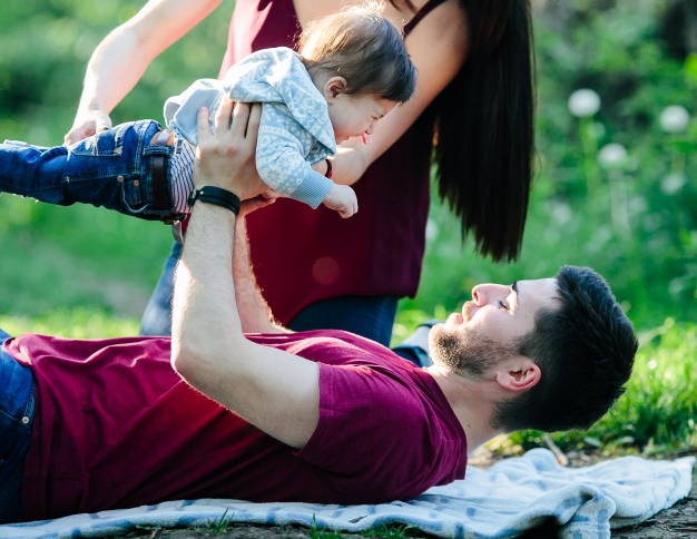 father-lying-in-a-park-with-his-baby-up-and-his-mother-helping-him_1153-2059.png