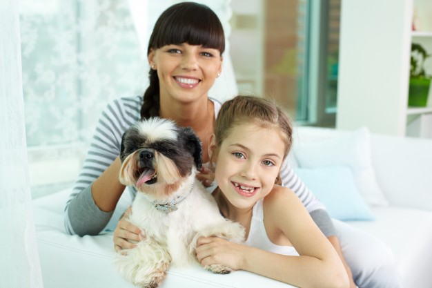 happy-girl-hugging-the-dog-with-her-mother_1098-2608