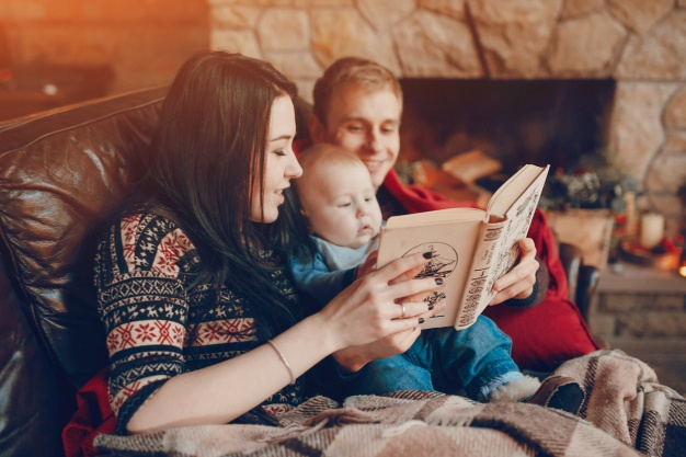 mother-and-father-reading-a-book-with-baby-in-the-middle_23-2147583290
