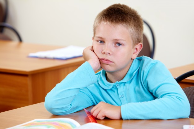 bored-little-boy-at-his-desk_1098-1955