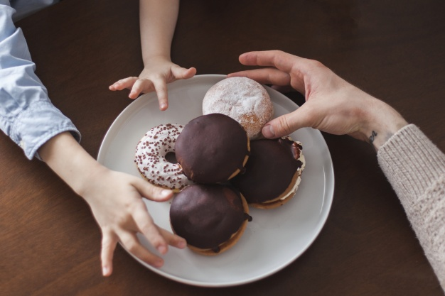 top-view-of-hands-next-to-some-donuts_23-2147624696.jpg