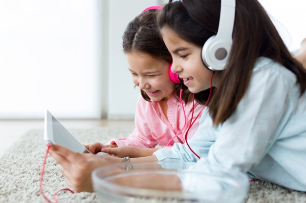 beautiful-young-sisters-listening-to-music-with-digital-tablet-a_1301-3911