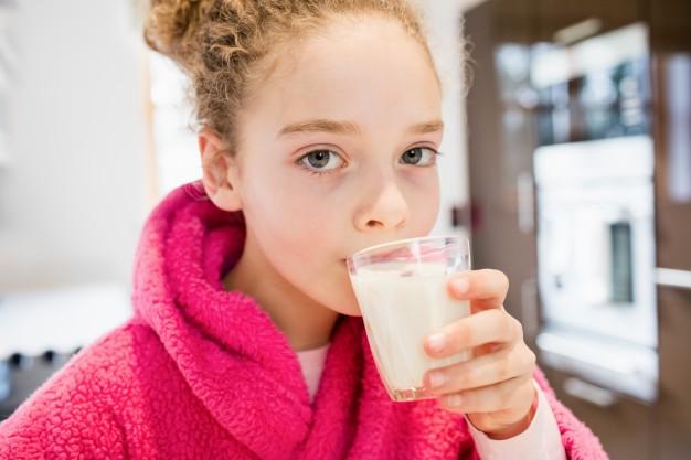 cute-girl-drinking-milk-in-kitchen_1170-2629